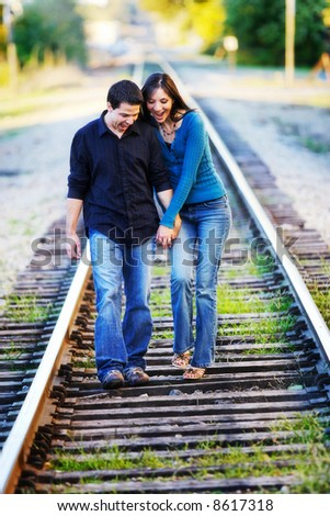 Couple walking in RR track. Laughing - stock photo