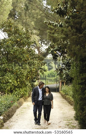 Couple walking inside a villa park - stock photo