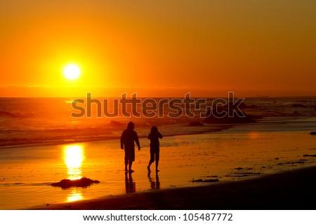 couple walking into the sunset - stock photo