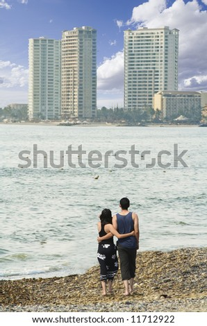 Couple walking on beach with high rise hotels - stock photo