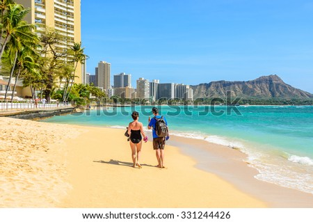 Couple walking on beach. Young happy interracial couple walking on beach talking holding around each other. - stock photo