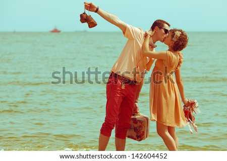 Couple walking on beach. Young happy married hipsters in trendy clothes kissing on beach and holding their shoes. Sunny summer day. Copy-space. Outdoor shot - stock photo