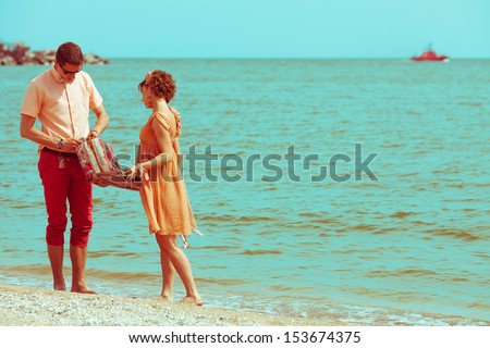 Couple walking on beach. Young happy married hipsters in trendy clothes talking on beach and holding their shoes. Sunny summer day. Copy-space. Outdoor shot