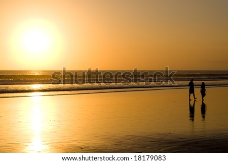 Couple walking on the beach at sunset. - stock photo