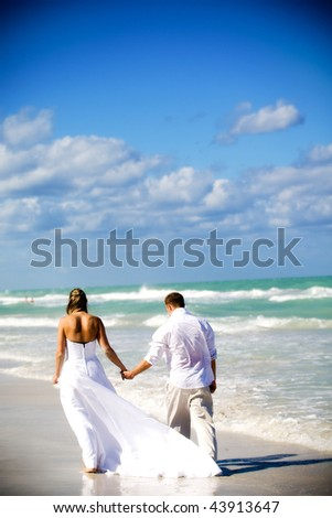 Couple walking on the beach at their destination wedding