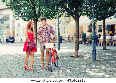Couple walking on the street with bike.  - stock photo