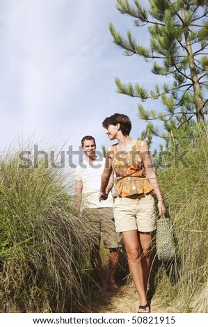 Couple walking on trail to beach - stock photo