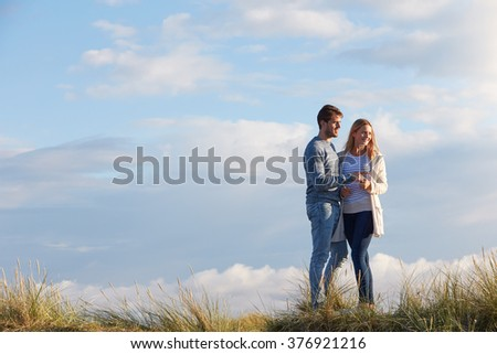 Couple Walking Through Sand Dunes Together - stock photo