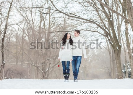 Couple walking with a rose in winter