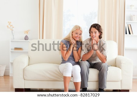 Couple watching a game on TV in their living room