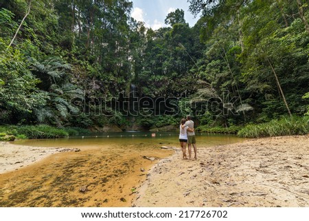 Couple watching a stunning multicolored natural pool in the thick rainforest of Lambir Hills National Park, Borneo, Malaysia. - stock photo