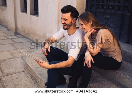 Couple watching digital touchscreen tablet ipad and laughing in the street - stock photo