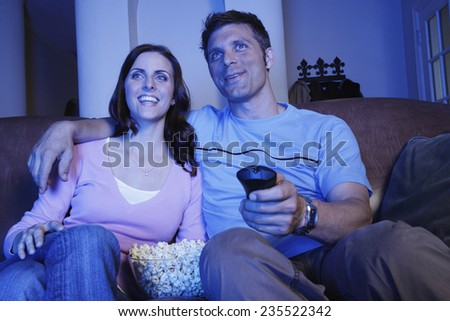 Couple Watching Movie and Eating Popcorn - stock photo