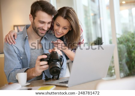 Couple watching photos on laptop computer - stock photo