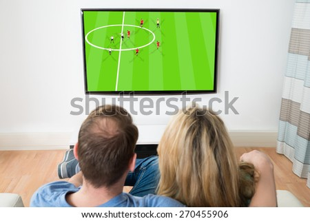 Couple Watching Sports On Television At Home - stock photo