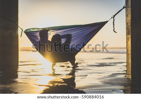 Couple watching sunset in hammock