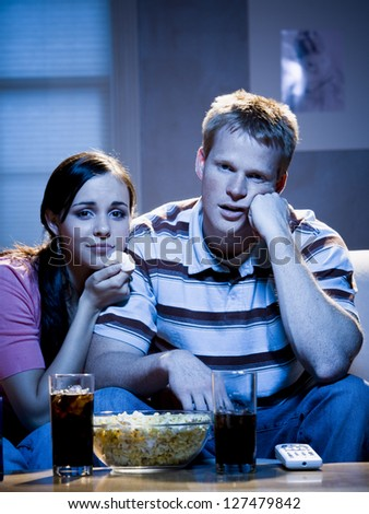 Couple watching television with bowl of popcorn and looking sad - stock photo