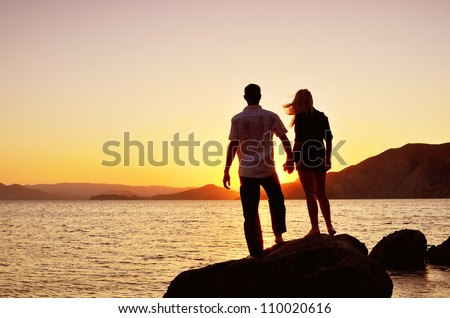 couple watching the sun by the sea while standing on a rock - stock photo