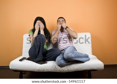 Couple watching TV a horror movie,woman cover eyes to not see anymore  while the young man are terrified - stock photo