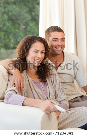 Couple watching tv in their living room at home - stock photo