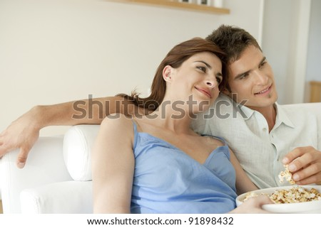 Couple watching tv together at home and eating popcorn.