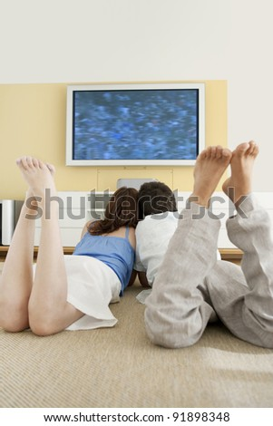 Couple watching tv together while laying down on the floor. - stock photo