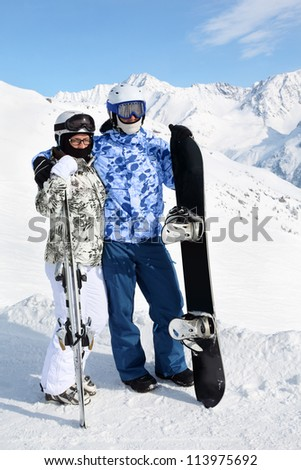 Couple wearing in sport suits and helmets stand with snowboard and skis on mountain. - stock photo