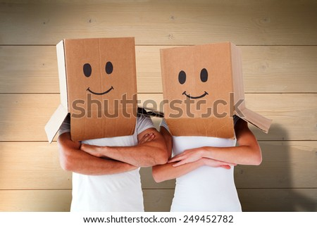 Couple wearing smiley face boxes on their heads against bleached wooden planks background - stock photo