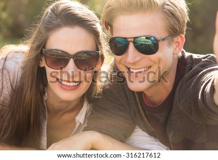 Couple wearing sunglasses taking a selfie together  - stock photo