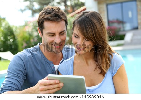Couple websurfing on internet with tablet - stock photo