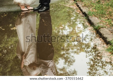 Couple, wedding, reflected in a puddle. Simplicity. Bride boho style.
