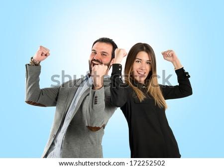 Couple winner over blue background. - stock photo