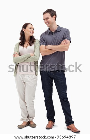 Couple with a complicit smile while crossing their arms against white background - stock photo