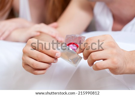 Couple with a condom in bed, horizontal - stock photo