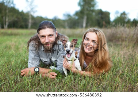 Couple with a dog sitting on the grass in the forest