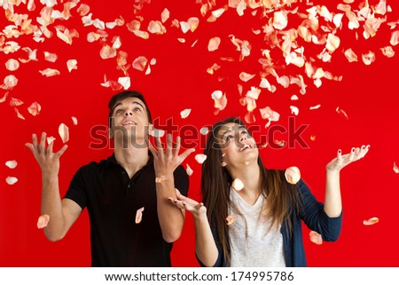 Couple with arms raised having fun throwing rose petals over red background. - stock photo