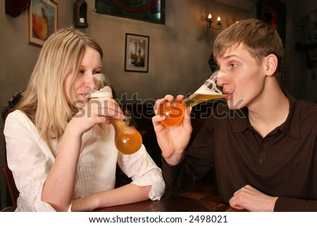 couple with beer in bar - stock photo