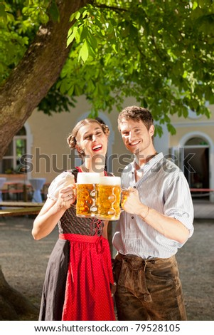 Couple with beer stein and traditional clothes in a beer garden - stock photo