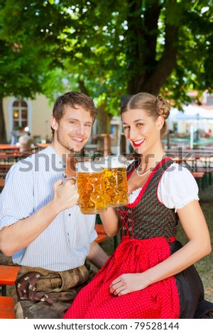 Couple with beer stein and traditional clothes in a beer garden