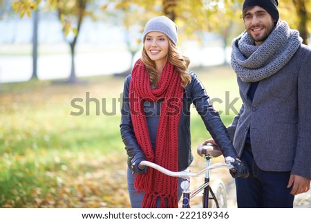 Couple with bike walking in autumn - stock photo