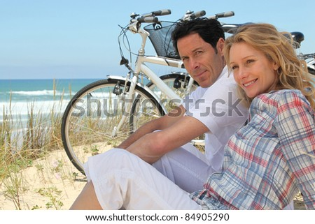 Couple with bikes sitting on the sand dunes - stock photo