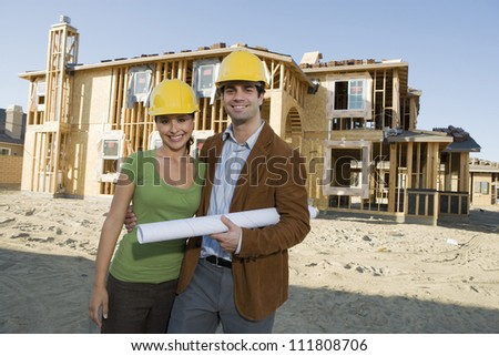 Couple with blueprint at construction site - stock photo