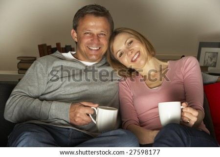 Couple With Coffee Mugs Watching Television - stock photo