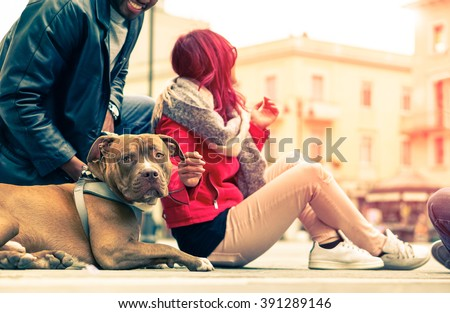 Couple with dog breed pit bull red nose relaxing in old town - Modern mixed carefree family - Concept of friendship between humans and animals - Cropped composition  vintage filter look with sun halo - stock photo
