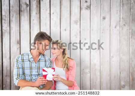 Couple with gift against wooden planks - stock photo