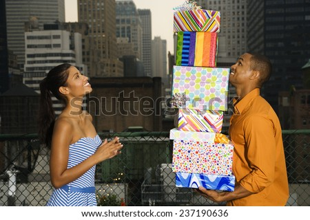 Couple with Gifts on Rooftop - stock photo