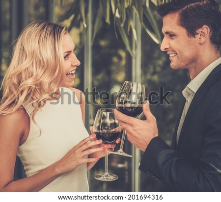 Couple with glasses of red wine in restaurant - stock photo