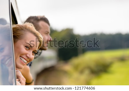Couple with heads out the train window excited woman man - stock photo