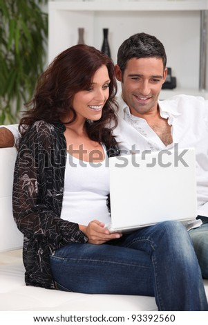 couple with laptop in lounge - stock photo