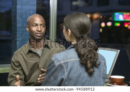 Couple with laptop talking at restaurant - stock photo